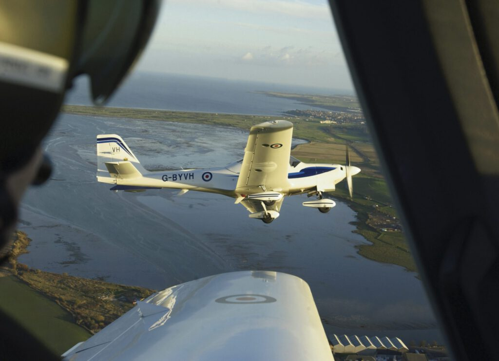 This image was submitted as part of the RAF Photographers Photographic Competition 2005.  Tutor Training Aircraft of the East Scotland University Air Squadron, 4 ship flight, with St Andrews in the distance.